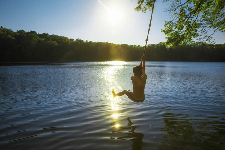 Lake Villa, IL Insurance - Young Boy in a Swimsuit Swings on a Rope Swing From a Tree Branch Into a Lake With the Sun Reflecting off the Water