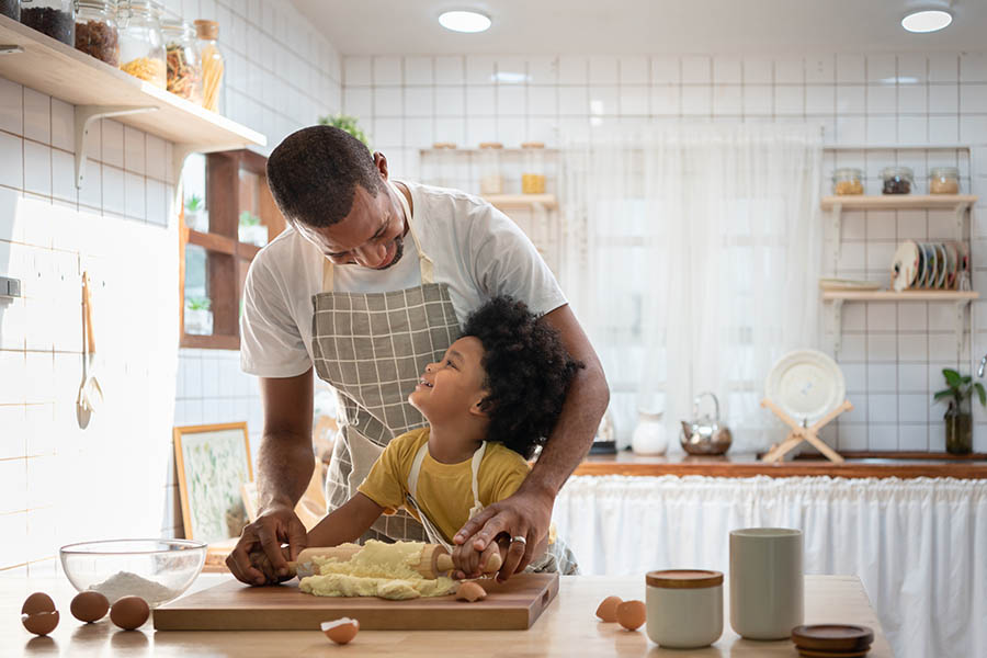 Personal Insurance - Father and Son Wearing Aprons Roll Out Cookie Dough in Their Country-Style Kitchen, With Eggshells and Baking Supplies Spread Out on a Wooden Counter