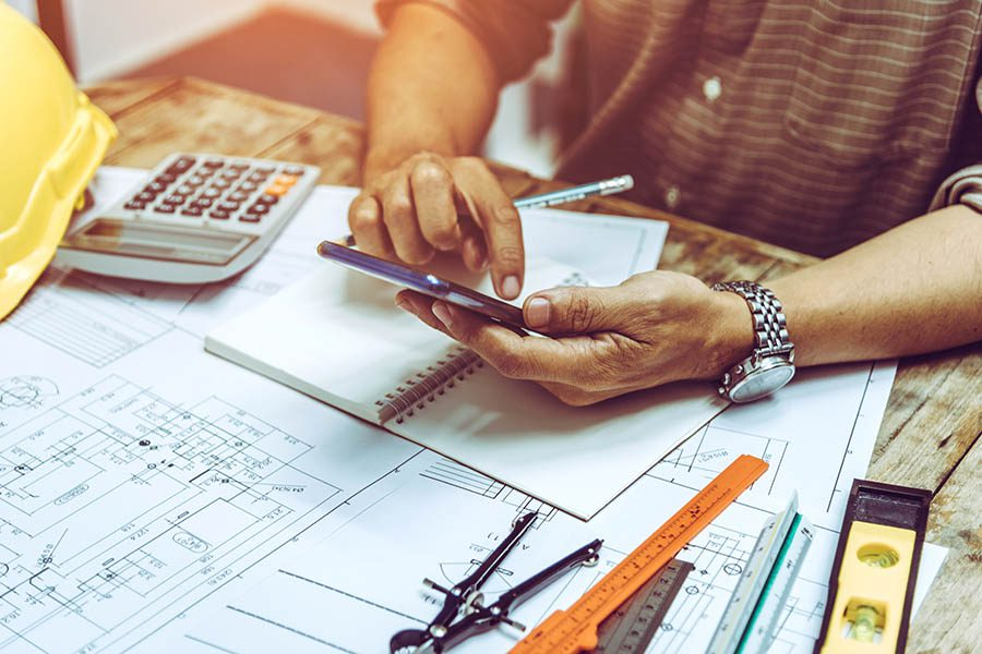 Specialized Business Insurance - Contractor Performs Calculations on His Phone With Drafting Tools, Hard Hat, and Calculator Spread Across His Wooden Desk