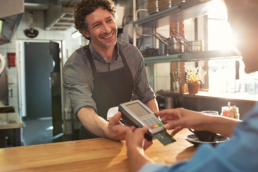 Business Insurance - Cheerful Small Business Restaurant Owner Taking Customers Credit Card Payment