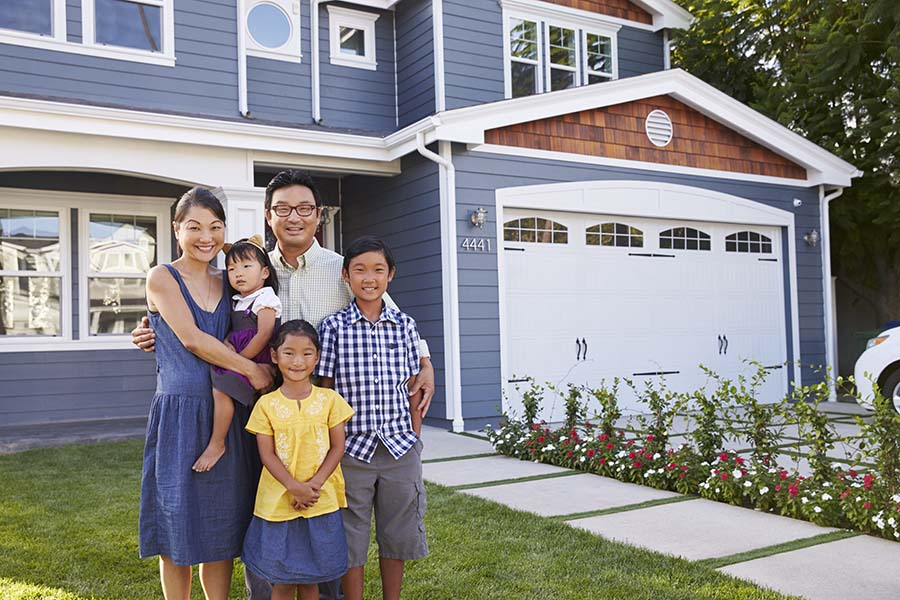 Personal Insurance - Portrait of a Smiling Family Standing Outside Their New Home