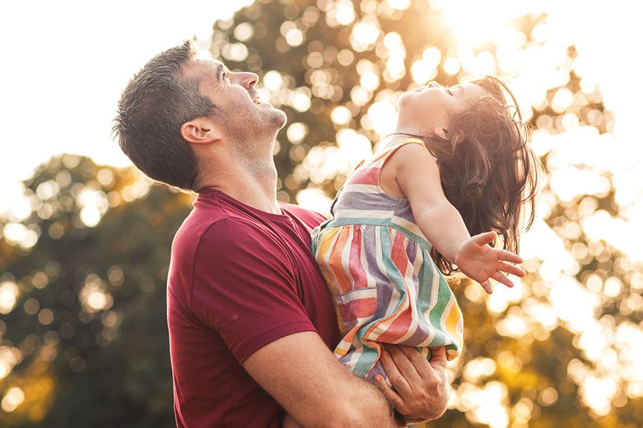 About Our Agency - Father Holding His Young Daughter Outside On Warm Day