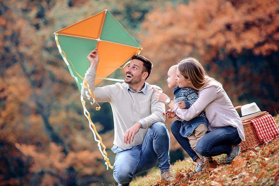 Blog - Happy Family Preparing To Fly A Kite At The Park