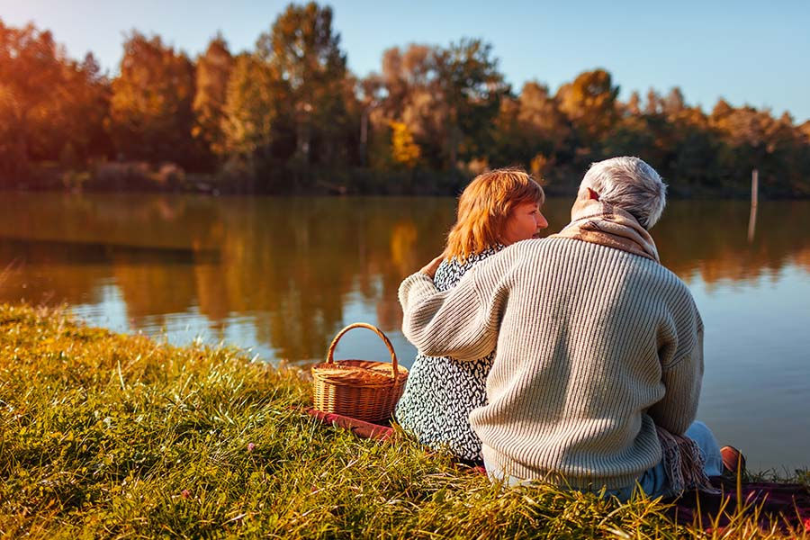 Contact - Older Couple Relaxing At The Lake During The Fall