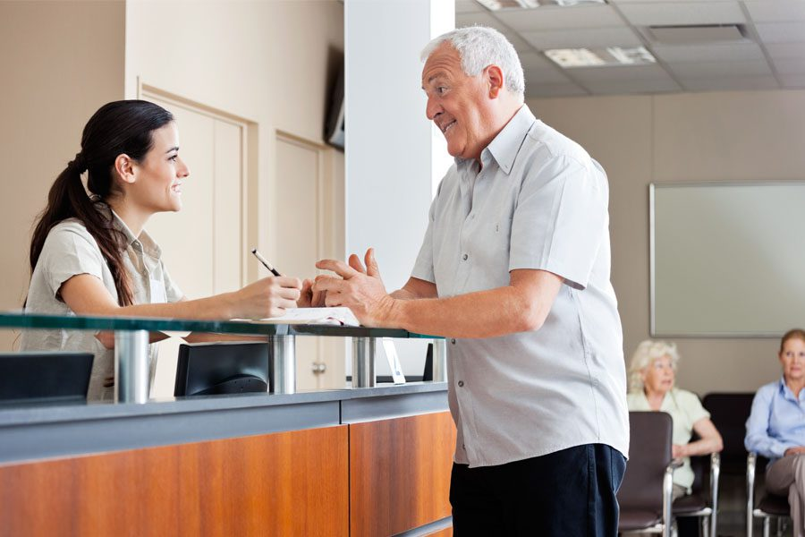 Medical Office Insurance - Receptionist and Patient Talking at the Front Desk