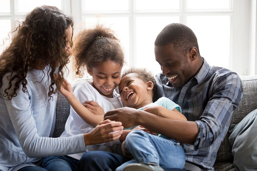 Personal Insurance - Family Sitting On Couch At Home Laughing And Playing Together