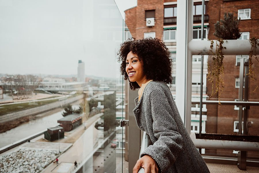 Personal Insurance - Young Woman Looking Out From Balcony In Apartment Building In The City