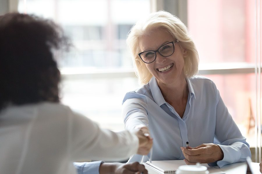 Refer A Friend - Mature Woman Sitting In Office Shaking Hands With Her Colleague
