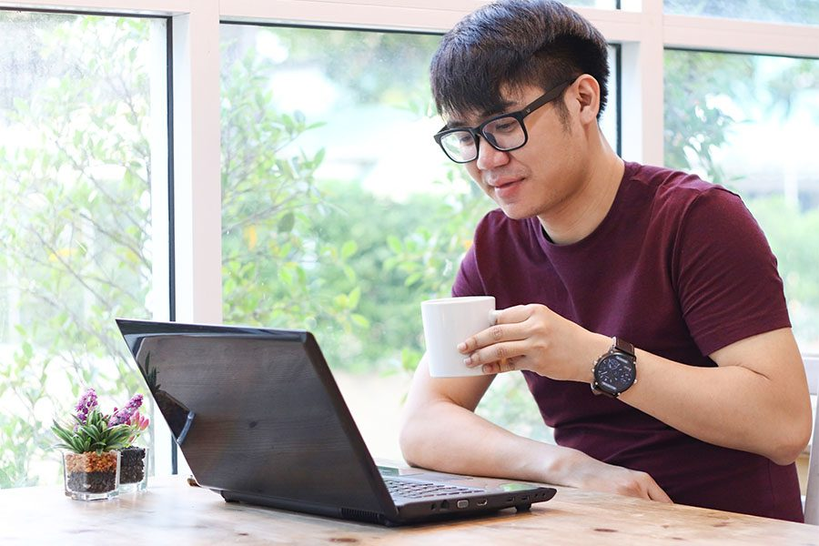 Report A Claim - Young Man Drinking Coffee And Working On His Laptop At Home
