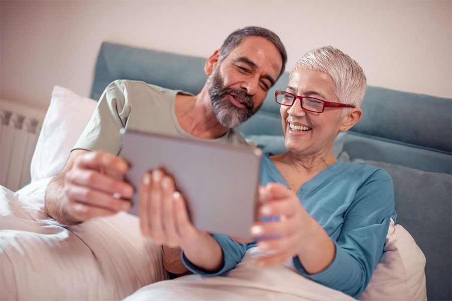 Request Policy Change - Smiling Mature Couple Sitting At Home Using Their Laptop