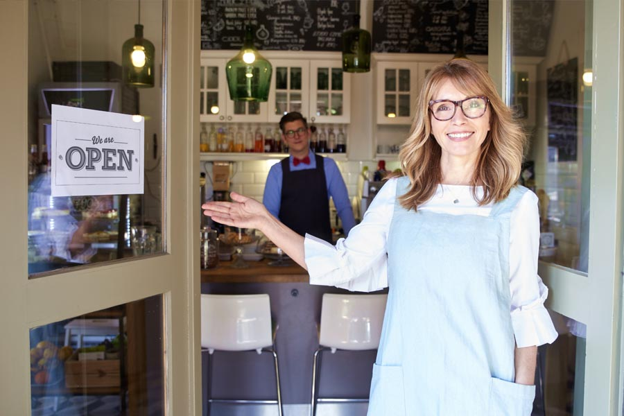 Business Insurance - Woman Business Owner Standing in Front of Her Shop Welcoming Customers In