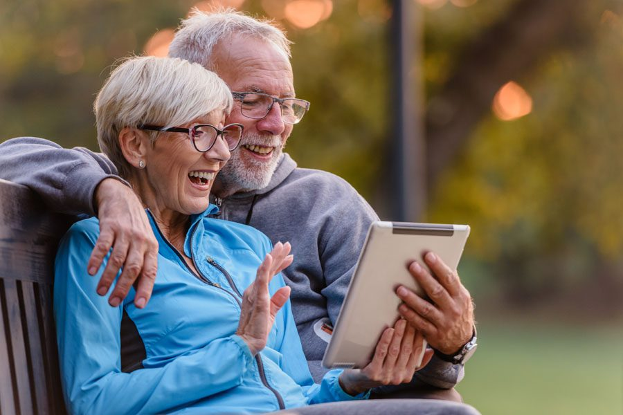 Client Center - Happy Older Couple Sitting on a Park Bench