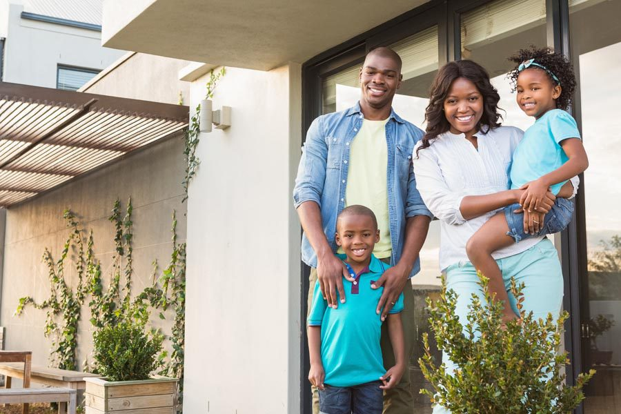 Personal Insurance - Family Standing in Front of Their Modern Home