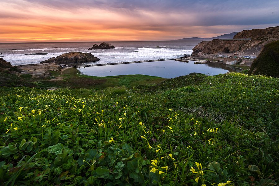 Contact - Sunset Over Rocks and Ocean Near Seal Beach in California