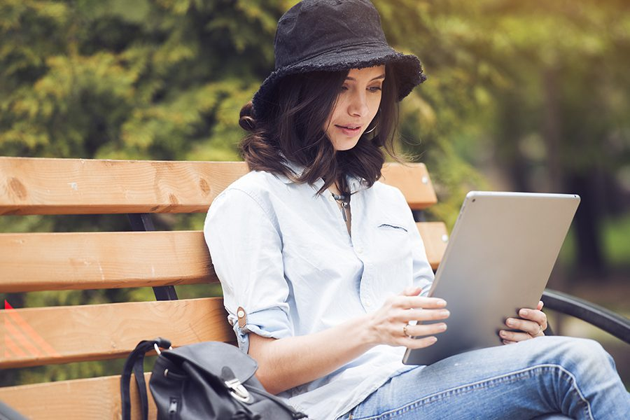 Client Center - Woman Using Her Tablet While in the Park