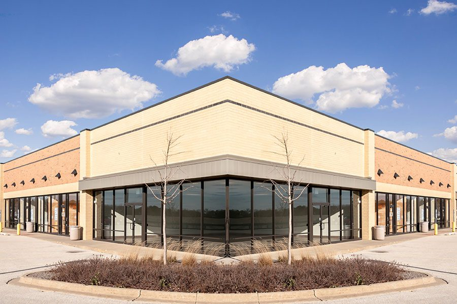 Business Insurance - New Commercial Retail Building Against Blue Sky