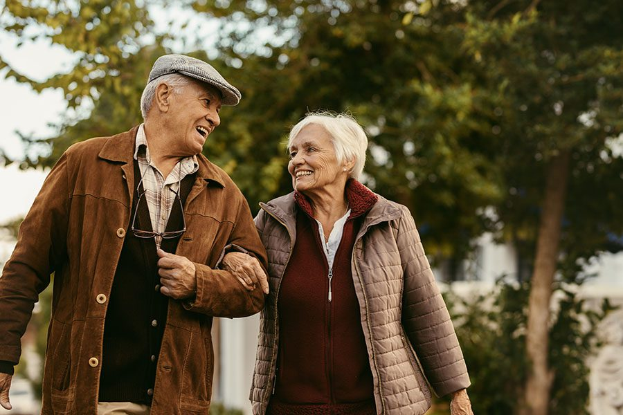 Employee Benefits - Smiling Elderly Couple Taking A Walk In The Winter Time
