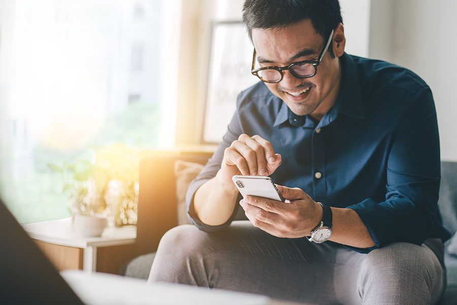 Insurance Quote - Happy Man Sitting On The Couch Using His Cellphone