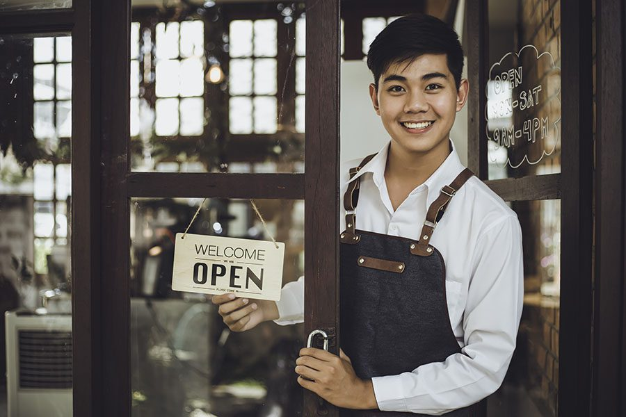 Business Insurance - Excited Young Business Owner Holding Up Open Sign On Front Window