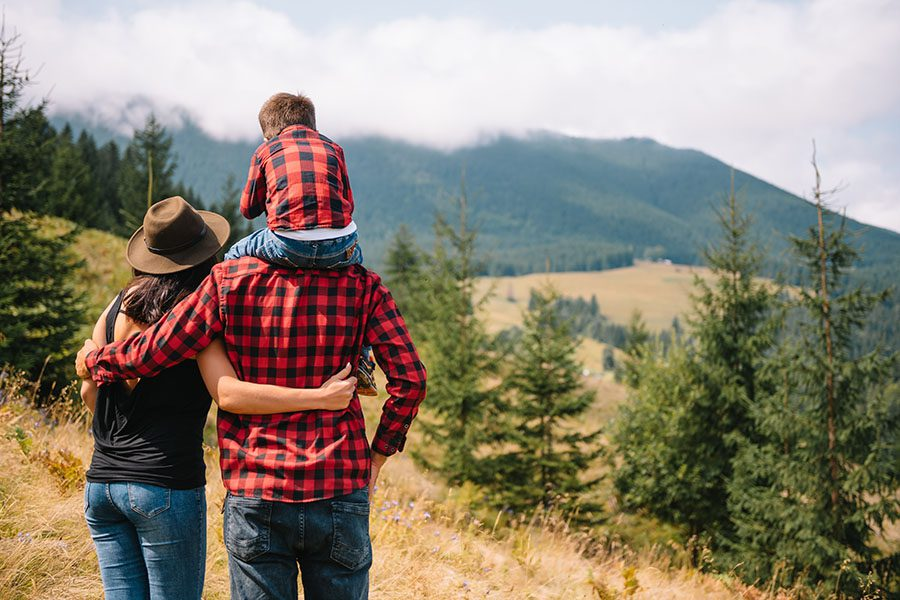 Personal Insurance - Family With Young Child Standing In The Meadow Enjoying The Views Of The Mountains And Valley