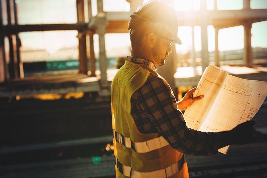 Specialized Business Insurance - Contractor Looking At Building Plans At Construction Jobsite