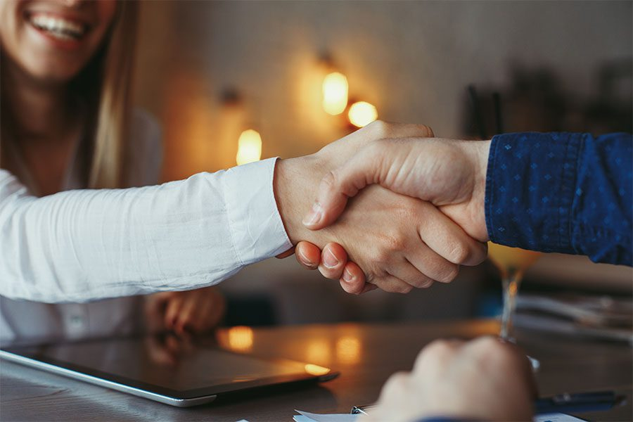 Community Engagement Referral Program - Insurance Agent Shaking Hands with a New Client in the Office