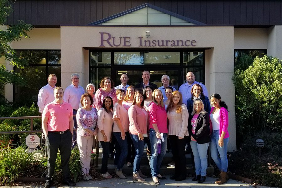Community Involvement - Portrait of Rue Insurance Team Standing Outside Office Celebrating Breast Cancer Awareness Month