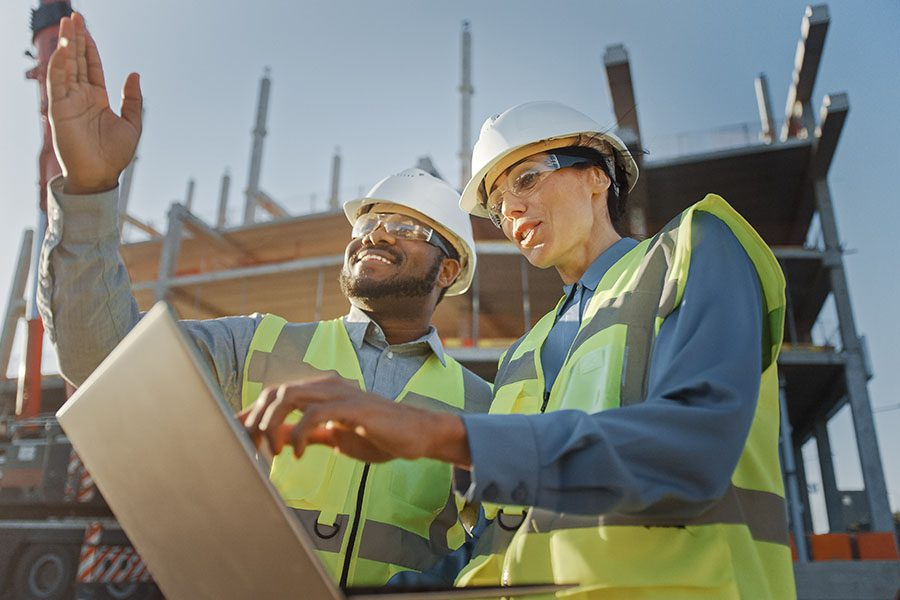 Specialized Small Business Insurance - View of Two Contractors Discussing Building Plans at Construction Jobsite