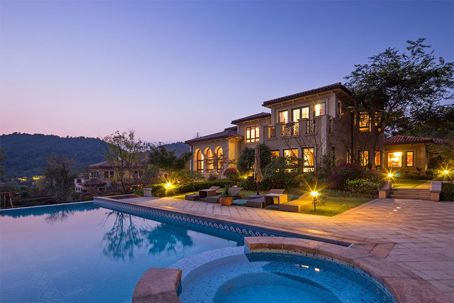 Private Client Services Insurance - View of Luxury Two Story Home with Swimming Pool in the Evening