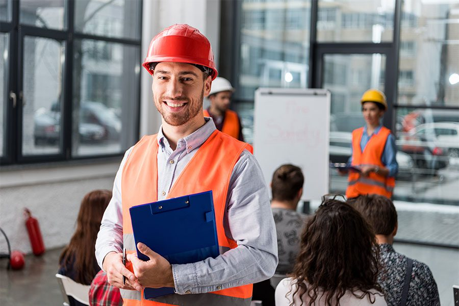 Safety Training and Certification - Portrait of a Cheerful Worker with a Clipboard Attending a Safety Presentation at Work