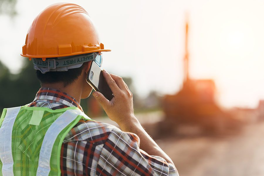 Client Center - Construction Worker Using a Phone on a Building Jobsite