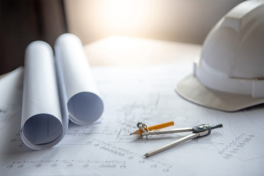 Specialized Business Insurance - View of Construction Hat and New Building Blue Prints on Desk