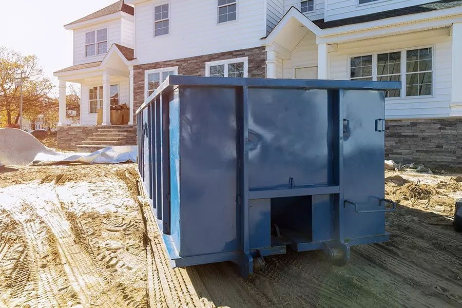 Roll-Off-Contractor-Insurance-Blue-Dumpster-in-Front-of-New-Home-for-Waste-and-Construction-Materials-at-Construction-Site