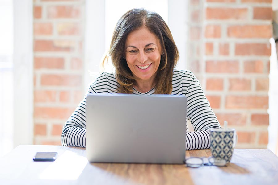 Blog - Mature Woman Smiles as She Uses a Laptop at a Wooden Table in Front of a Brick Wall With Coffee and Glasses by Her Side