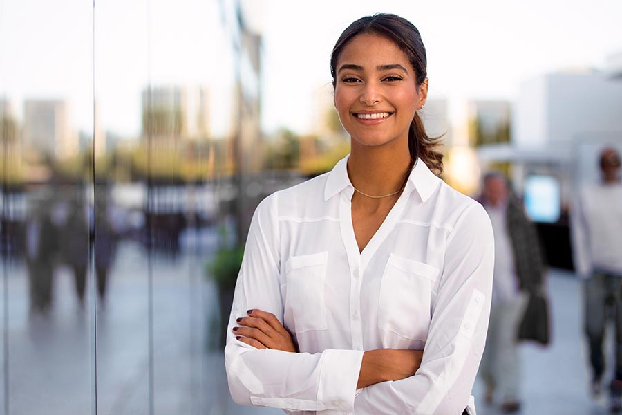 Business Insurance - Businesswoman in Dress Shirt Smiles With Arms Crossed Outside of an Office Building