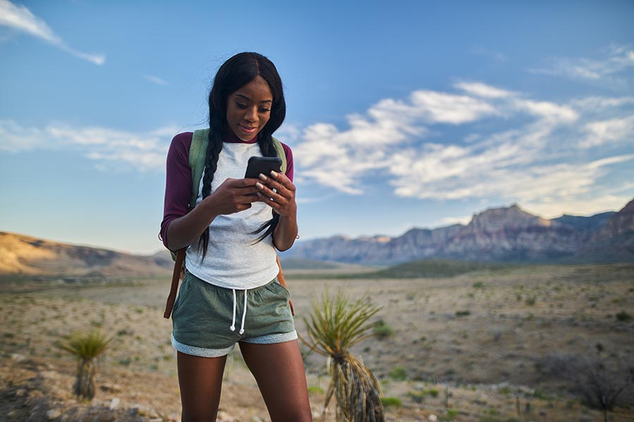 Contact Us - Young Woman Makes a Call While Hiking in the Southwest, Hair in Pigtails, Wearing Shorts and a Backpack