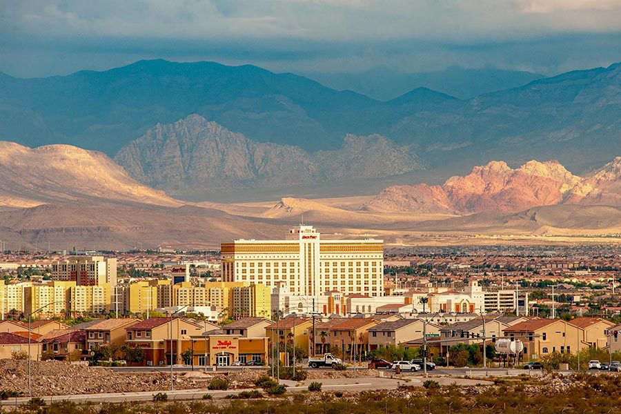 Henderson, NV Insurance - View of Hotels and Homes in Henderson, Nevada From a Distance, the Mountains Rising in the Background Under a Stormy Sky