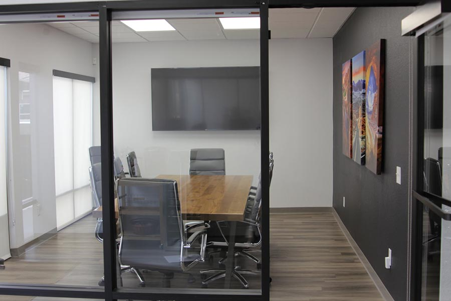 Office Tour - Conference Room Exterior Showing Large Conference Room Table, Chairs, Large Screen Television, Black Accent Wall and Southwest Artwork