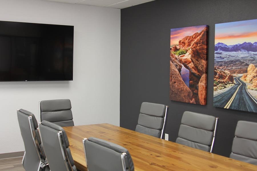 Office Tour - Conference Room Interior Showing Large Conference Room Table, Chairs, Large Screen Television, Black Accent Wall and Southwest Artwork