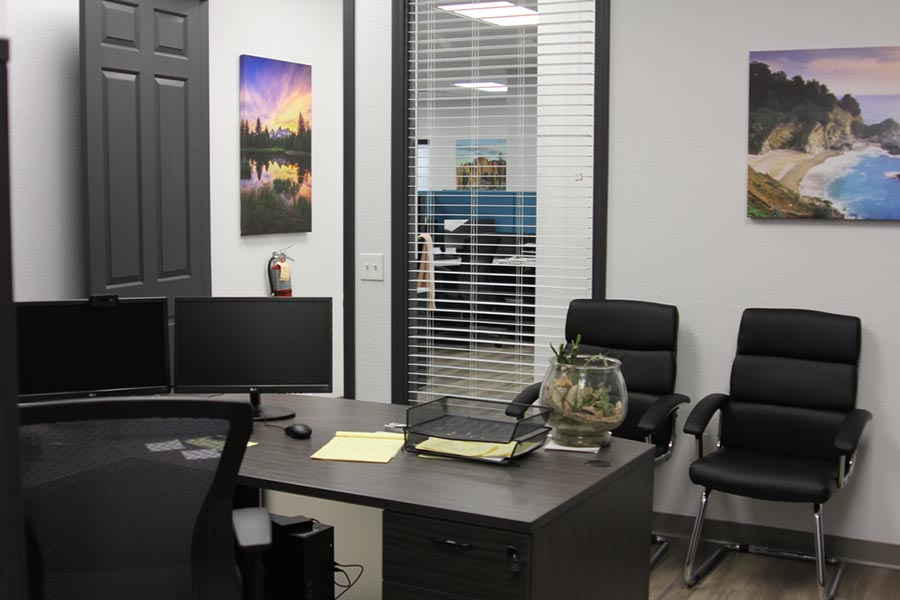 Office Tour - Office Interior with Dual Monitors and Paperwork on Desk, Black Chairs and Southwest Artwork