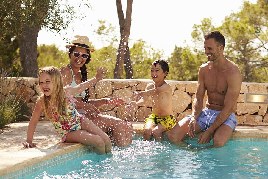 Personal Insurance - Family Splashes Each Other While Sitting on the Edge of Their Pool, Son and Daughter Seated Next to Their Parents
