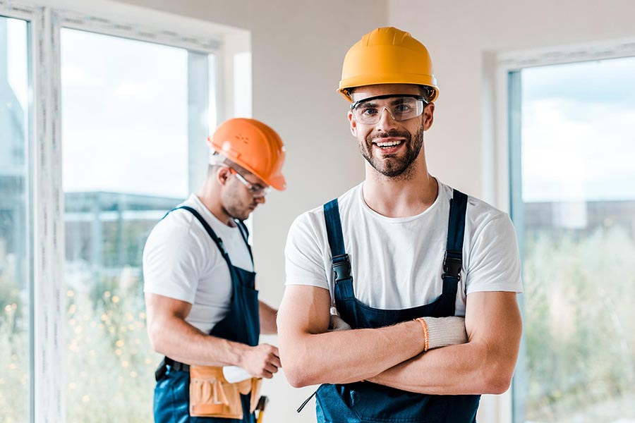 Specialized Business Insurance - Two Construction Workers Stand in an Unfinished Home, Wearing Blue Overalls and Orange Hardhats