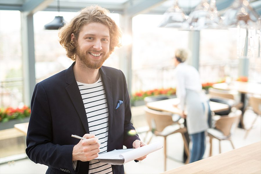 Specialized Business Insurance - Portrait of a Restaurant Owner Smiling at Camera with Fellow Employee Working in the Background with Tables and Chairs