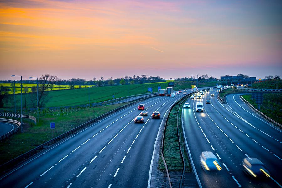 About Our Agency - Long Exposure of a Busy Highway at Sunset, Green Fields and Trees on Each Side, Cars and Trucks With Lights on Speeding Past
