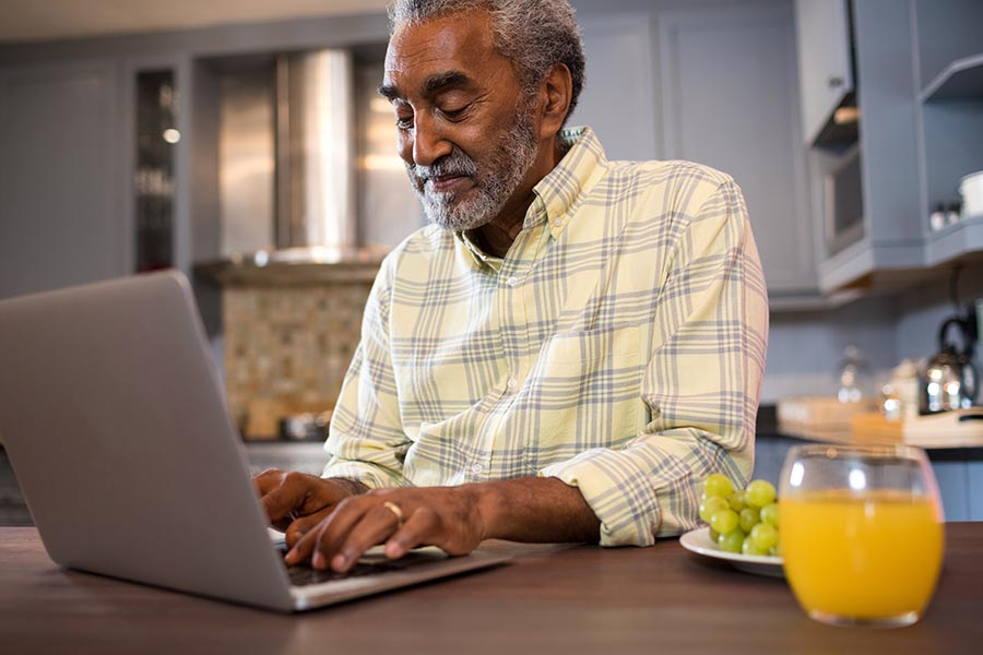 Contact Us - Senior Man Happily Using Computer at Wooden Kitchen Table With a Glass of Orange Juice and Plate of Grapes Beside Him