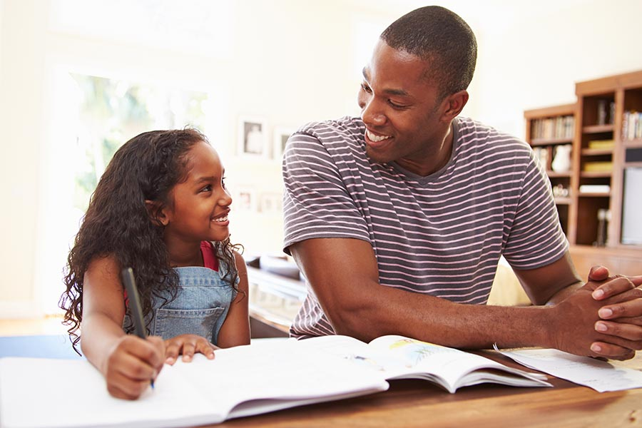 Personal Insurance - Father and Young Daughter Smile at Each Other as He Helps Her With Her Homework at the Kitchen Table