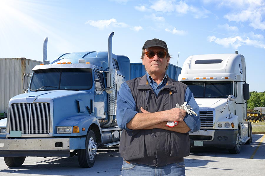 Specialized Business Insurance - Serious Truck Driver in Hat, Sunglasses, Vest and Jeans Crosses His Arms While Standing in Front of Large Trucks
