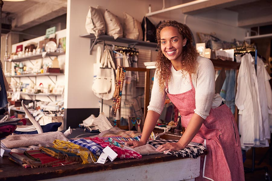 Business Insurance - Shop Owner Organizes Scarves for Sale in a Boutique Filled With Homegoods and Clothing