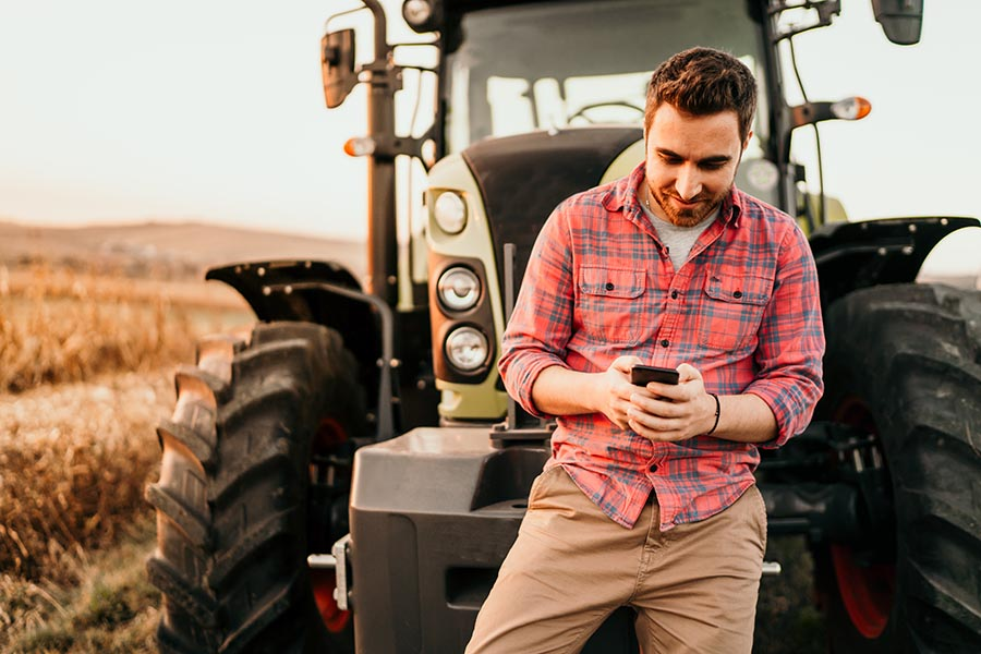 Contact Us - Young Farmer Leans Against Tractor in a Field, Making a Phone Call