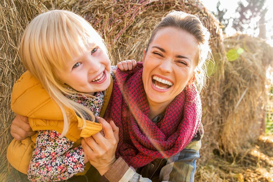 Personal Insurance - Mother and Young Daughter Sit in Front of Hay Bales, Smiling and Hugging, Wearing Fall Clothing
